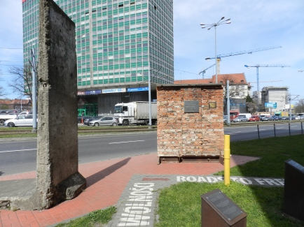 a piece of the Berlin Wall next to a piece of the original shipyard wall